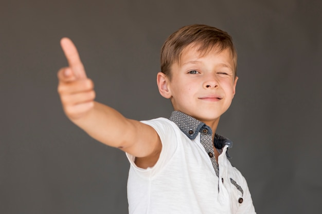 Chłopiec robi pistoletowi z jego palcami