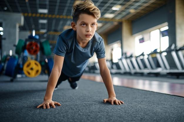 Chłopiec robi push up ćwiczenia w siłowni, widok z przodu. młodzik na treningu w klubie sportowym, służbie zdrowia i zdrowym stylu życia, uczeń na treningu, młodzież sportowa