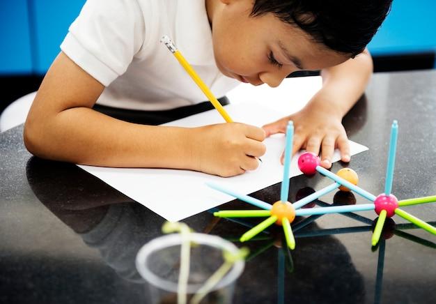 Chłopiec robi schoolwork w laboratorium naukowym