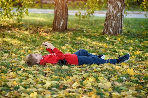 Chłopiec robi zdjęcia leżąc na plecach. trawnik z jesiennymi liśćmi. słoneczny dzień