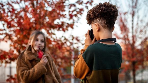 Chłopiec robi zdjęcie swojemu przyjacielowi w parku