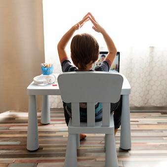 Chłopiec rozmawia ze swoim nauczycielem i wskazuje szkołę internetową