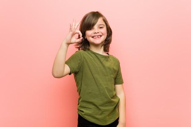 Chłopiec rozochocony i ufny pokazuje ok gest.