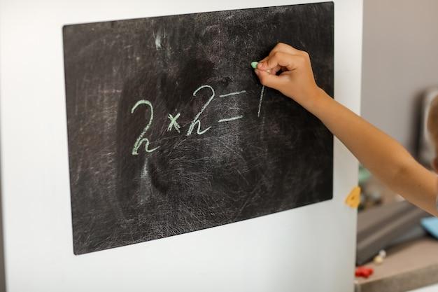 Chłopiec rozwiązuje matematykę w domu na desce kreślarskiej