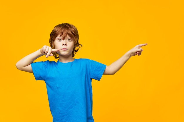 Chłopiec rude włosy niebieski t-shirt żółte na białym tle piegi i wskaż palcem w bok, ładna buźka