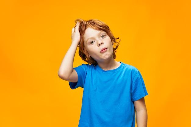 Chłopiec rude włosy niebieski t-shirt żółte na białym tle piegi i zaskoczony wygląd oszołomiony