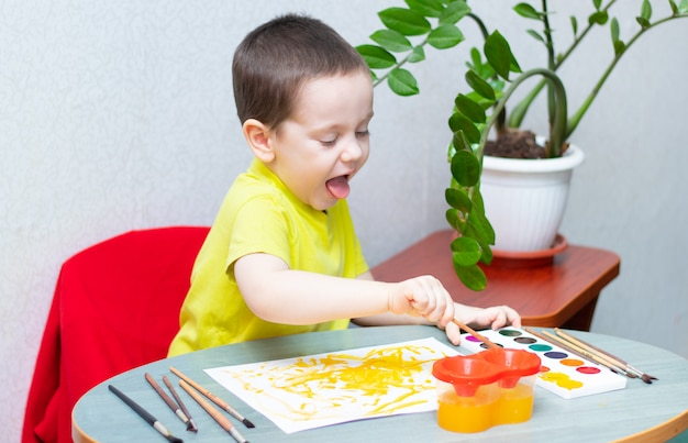 Chłopiec rysuje farbami