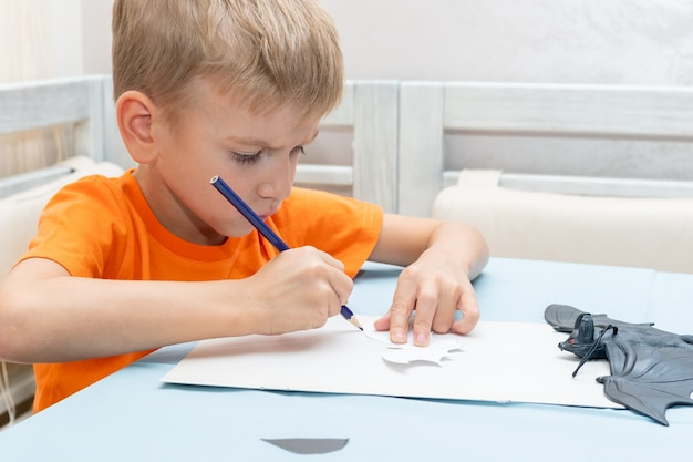 Chłopiec rysuje i wycina w domu dekorację na halloween z czarnego papieru. diy dekoracje rzemieślnicze. dziecko robi czarne nietoperze z papieru, origami