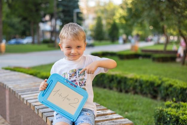 Chłopiec rysuje i zapisuje liczby na tablicy