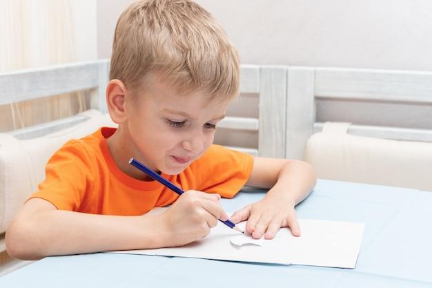 Chłopiec rysuje kontur, rysuje dekorację na halloween w domu z papieru. diy dekoracje rzemieślnicze. dziecko robi czarne nietoperze z papieru, origami