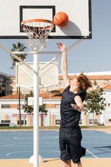 Chłopiec rzuca w obręcz do koszykówki