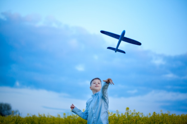 Chłopiec rzuca zabawkarskiego samolot w letnim dniu.