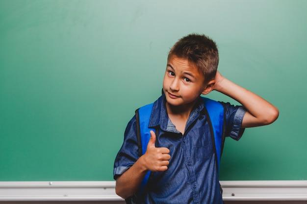 Chłopiec scratching głowy i gesturing kciuk do góry