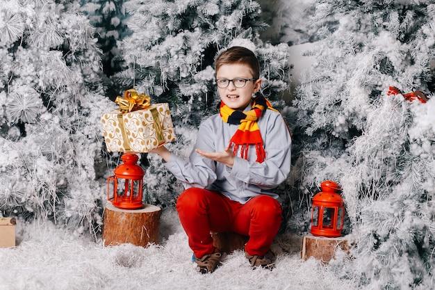 Chłopiec siedzący na podłodze nie lubi prezentu świątecznego