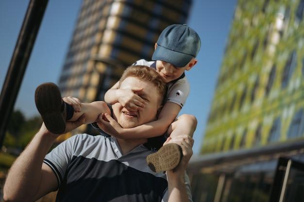 Chłopiec siedzący na ramionach ojca zamykający oczy rękami bawiący się z rodziną w mieście