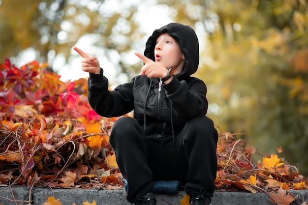 Chłopiec siedzący w pięknym jesiennym parku pokazuje się z boku ręką.
