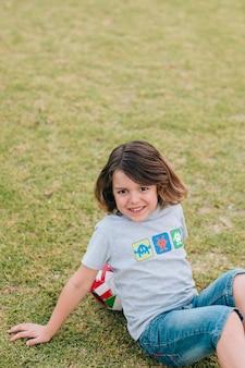 Chłopiec siedzi i opiera na futbolu