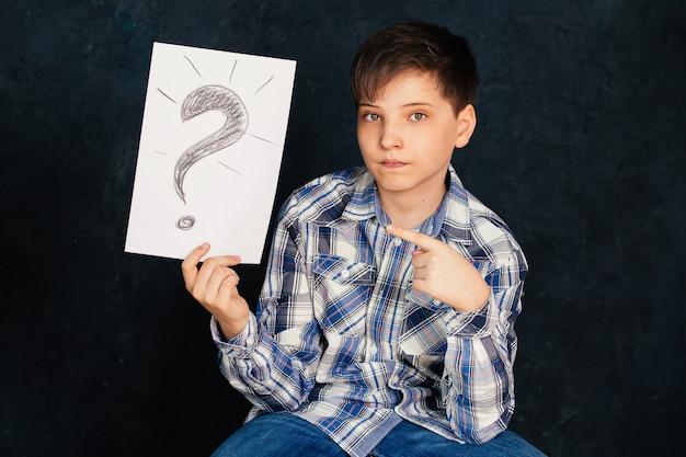 Chłopiec siedzi i trzyma biały papier ze znakiem zapytania