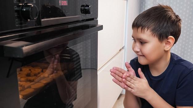 Chłopiec siedzi i zagląda do piekarnika, czekając na ciastko