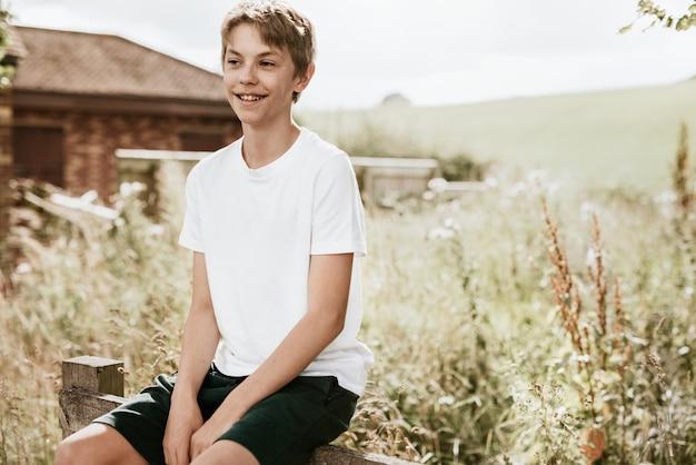 Chłopiec siedzi na drewnianym płocie, letnie wakacje