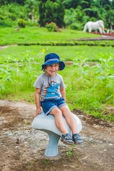Chłopiec siedzi na dużym grzybie