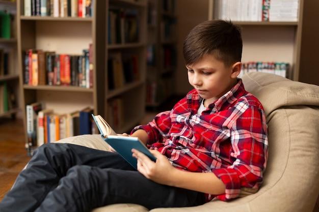 Chłopiec siedzi na kanapie i czytaniu