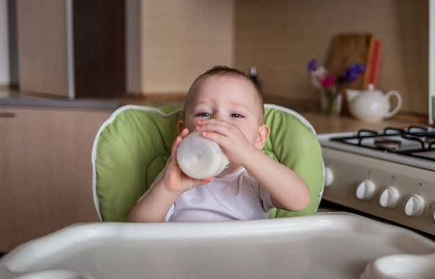 Chłopiec siedzi na krześle do karmienia i pije z butelki
