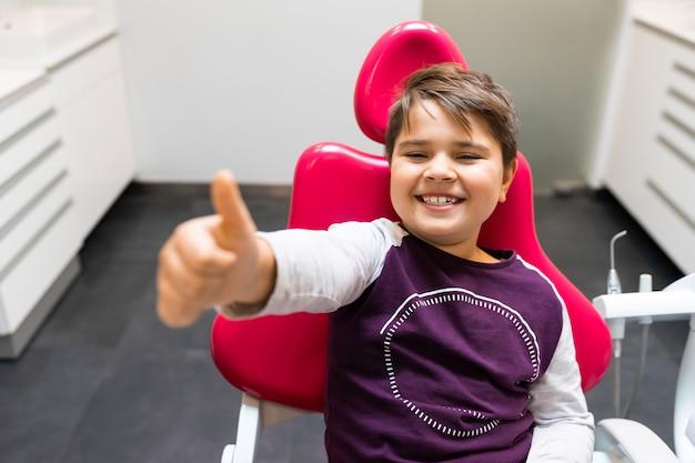 Chłopiec siedzi na krześle u dentysty i pokazuje kciuk do góry
