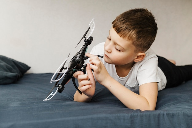 Chłopiec siedzi na łóżku i bawi się dronem