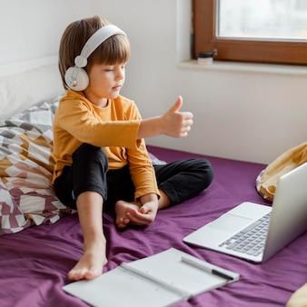 Chłopiec siedzi na łóżku i nauka kciuki do góry