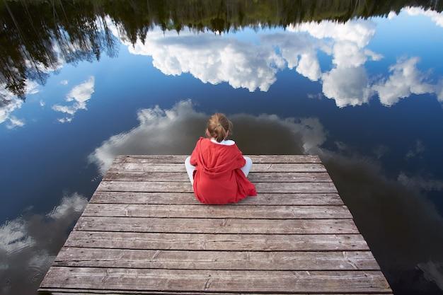 Chłopiec siedzi na molo i patrząc na jezioro