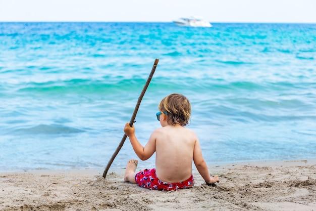 Chłopiec siedzi na piasku na plaży, tyłem do aparatu