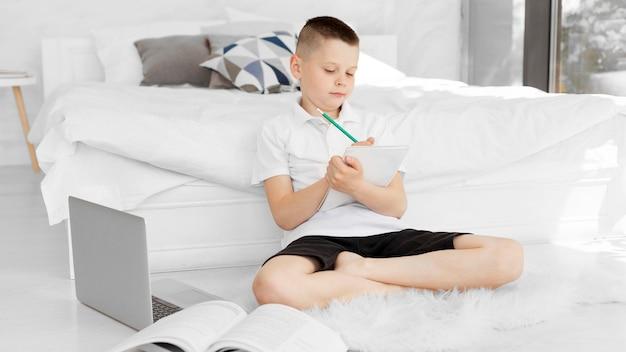 Chłopiec siedzi na podłodze i pisze notatki