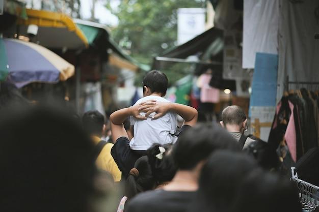 Chłopiec siedzi na ramionach ojca