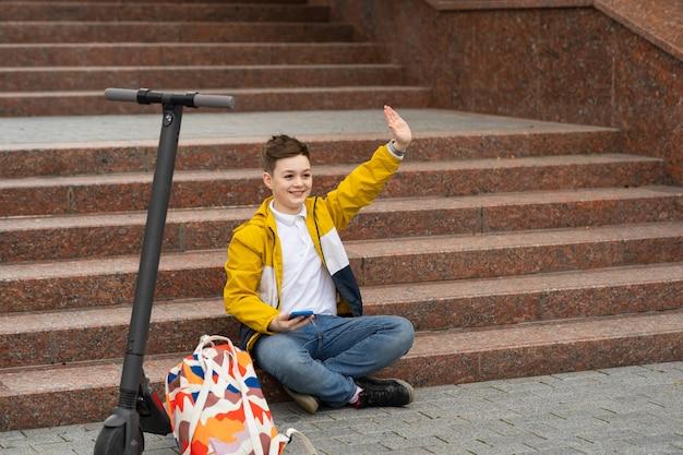 Chłopiec siedzi na schodach w pobliżu skutera elektrycznego i macha