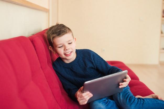 Chłopiec siedzi na sofie z tabletem