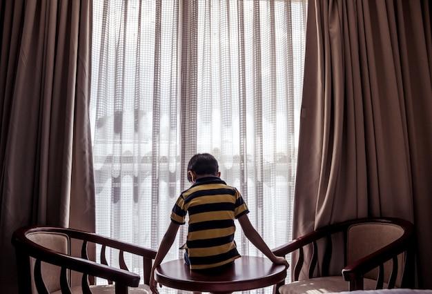 Chłopiec siedzi na stole patrząc w dół