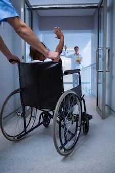 Chłopiec siedzi na wózku inwalidzkim i macha ręką do lekarza w korytarzu
