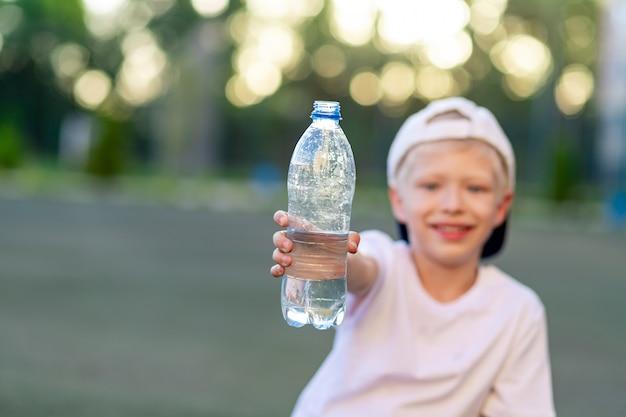 Chłopiec siedzi na zielonym trawniku na boisku piłkarskim i trzyma butelkę wody. skoncentruj się na butelce z wodą.