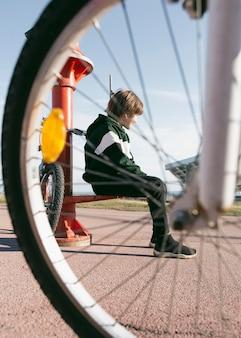 Chłopiec siedzi obok teleskopu na zewnątrz z rowerem