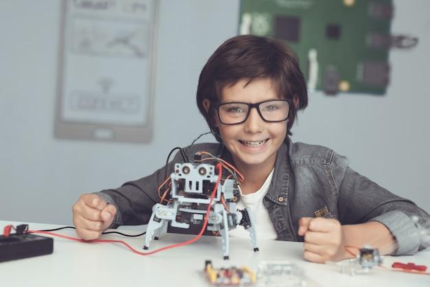 Chłopiec siedzi przy biurku i konstruuje robota w domu