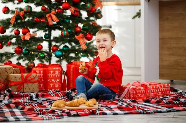 Chłopiec siedzi przy choince w świątecznej kuchni. w rękach trzyma rogalika. przytulne zimowe wieczory w domu. pod choinką jest wiele prezentów świątecznych