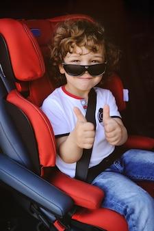 Chłopiec siedzi w czerwonym foteliku samochodowym