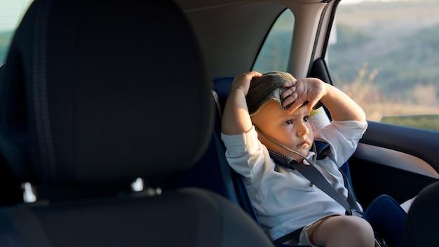 Chłopiec siedzi w foteliku dla dziecka lub dziecka z tyłu samochodu w słońcu z ręką na głowie