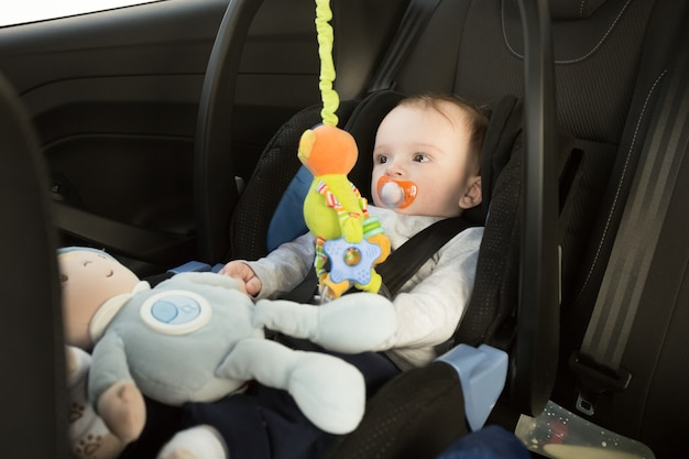 Chłopiec siedzi w foteliku samochodowym i bawi się zabawkami