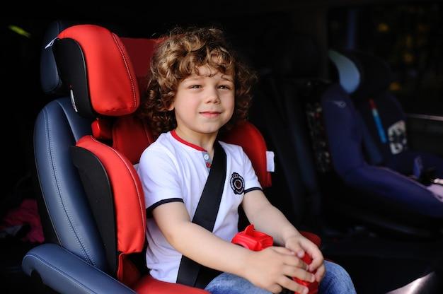 Chłopiec siedzi w foteliku samochodowym