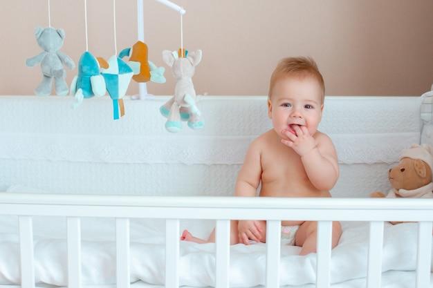 Chłopiec siedzi w łóżeczku dziecięcym w pieluchy