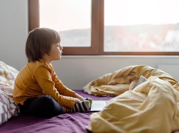 Chłopiec siedzi w łóżku i nauka