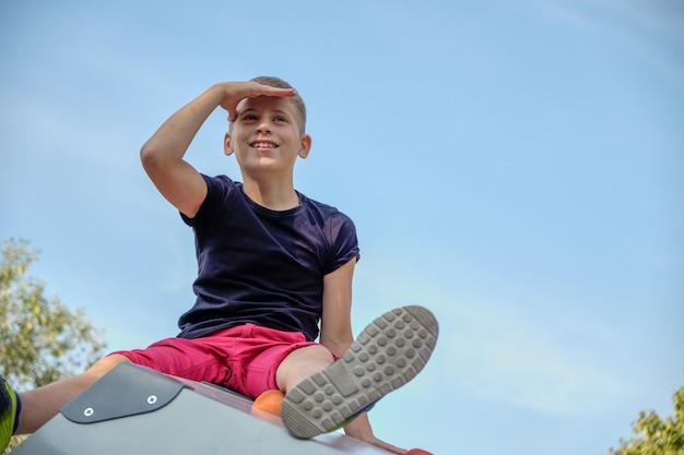 Chłopiec siedzi w parku na wzgórzu i patrzy daleko w kierunku niebieskiego nieba. skopiuj miejsce