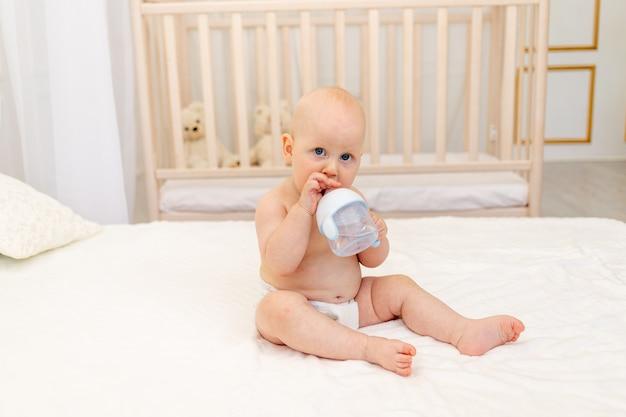 Chłopiec siedzi w pieluchach na białym łóżku
